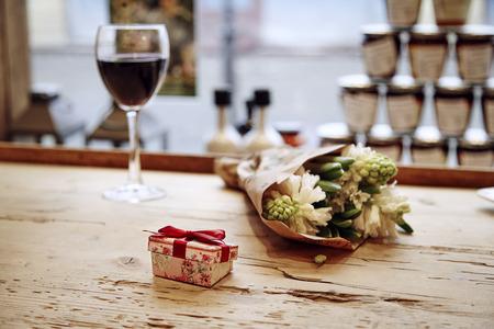 Petite boîte présente mignon avec arc à table en bois, des fleurs et verre de vin derrière. réunion romantique dans le café. Le concept de la Saint-Valentin jour. Banque d'images