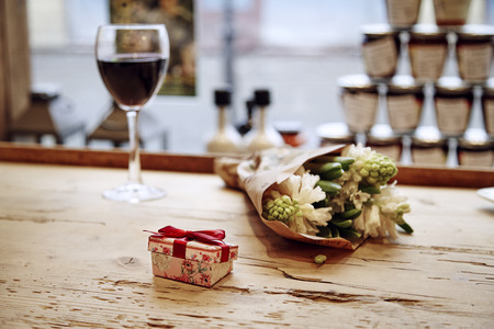 Small cute present box with bow at wooden table, flowers and glass of wine behind. Romantic meeting in cafe. St. Valentines day concept.