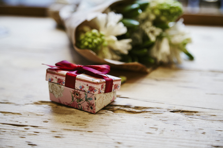 Small cute present box with bow at wooden table, rose flowers behind. St. Valentines day concept.