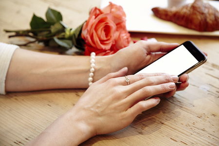 Close-up of woman beautiful hands holding mobile phone. Blank phone screen for layout. Red roses flowers behind on wooden table. St. Valentines day concept.