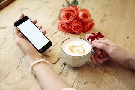 Cup of coffee and mobile phone in beautiful woman hands. Blank screen for layout. Red roses flowers behind on wooden table. St. Valentines day concept. Archivio Fotografico