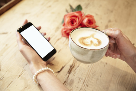 Cup of coffee in beautiful woman hands. Lady using mobile phone internet in cafe. Blank screen for layout. Red roses flowers behind on wooden table. St. Valentines day concept