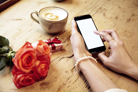Mobile phone in beautiful woman hands. Lady writing message. Red roses flowers and present box behind on wooden table. St. Valentines day concept