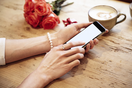 Mobile phone in beautiful woman hands. Lady using internet in cafe. Red roses flowers behind on wooden table. St. Valentines day concept Banque d'images