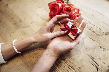 Piccolo carino scatola presente con arco in bella donna mani. Focus sulla prua. Rose rosse fiori dietro su tavola di legno. concetto di giorno di San Valentino