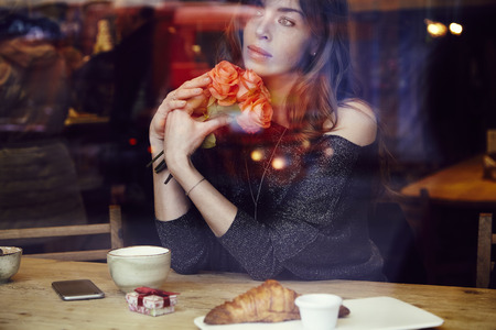 Beautiful woman with long hair holding red roses flowers in hand look through the window in cafe. Coffee and croissant on wooden table. St. Valentines Day or Birthday concept. Stock Photo