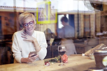 Beautiful blonde woman wearing eyeglasses messaging by mobile phonein cafe. Got a love message. Present box and rose flowers on wooden table. Romantique breakfast for a date or St. Valentines Day. Stock Photo