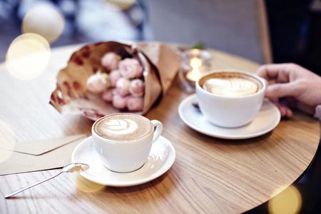 Due tazze di caffè con cuore e fiori sul tavolo di legno in caffetteria. Man mano che regge una coppa. Bokeh su sfondo. Concentrarsi sulla tazza di caffè.