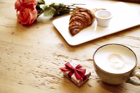 Casella attuale, rosa fiori, croissant freschi, caffè sul tavolo di legno. Prima colazione romantica per San Valentino festeggiare.