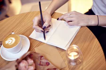 close-up of woman hands writing in notebook, blank pages for layout. Focus on hands.Cappuccino latte coffee with heart on top. Flowers on wooden table in modern cafe. St. Valentines celebration concept