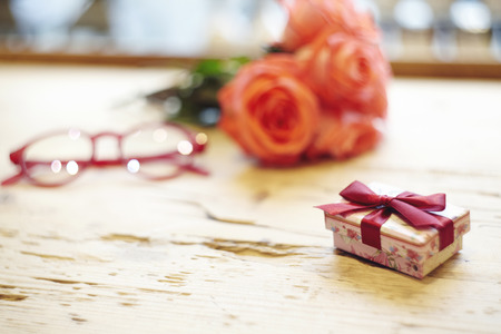 Small present box with bow on wooden table. Focus on bow. Red roses flowers behind on wooden table. St. Valentines day concept. Blank space for text