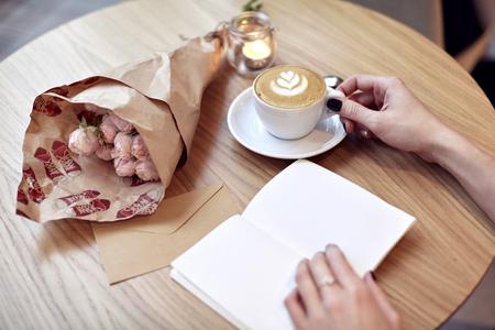 Cappuccino caffè del latte in mano della donna con il cuore in cima. Fiori sul tavolo di legno in caffetteria moderna. San Valentino celebrazione concetto