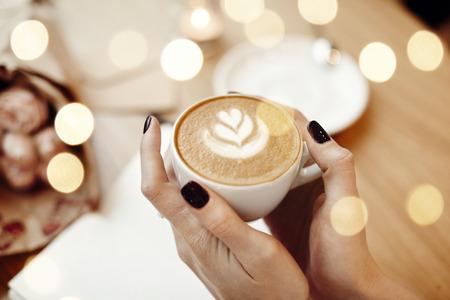 Tasse de café cappuccino dans les mains de femme, vue de dessus, bokeh, fleurs roses dans le café