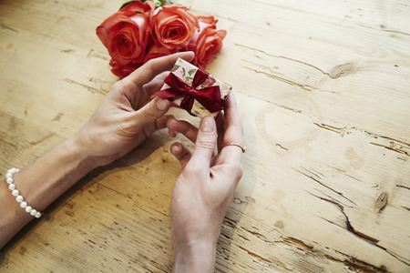 Small present box with bow in beautiful woman hands. Focus on bow. Red roses flowers behind on wooden table. St. Valentines day concept Stock Photo