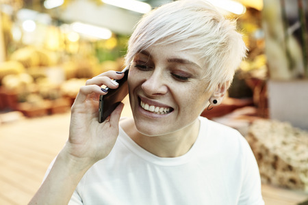 Portrait of  hipster woman with blonde short hair happy talking by mobile phone. Indoor botanical garden interior or summer park Banque d'images