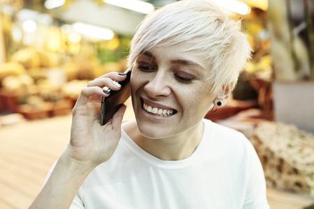 Ritratto di donna pantaloni a vita bassa con bionda capelli corti felice parlando dal telefono cellulare. Indoor interno orto botanico o parco estate