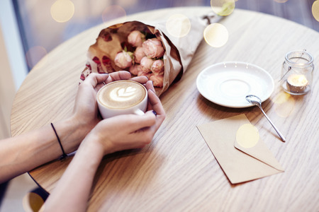 Cup of coffee with heart in woman hands, envelope and flowers on wooden table in cafe. Bokeh on background. Focus on left hand. Stock Photo
