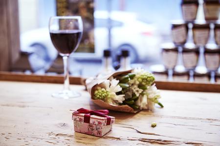 Piccola casella presente con arco e bouquet di fiori sul tavolo in legno. concetto di giorno di San Valentino.