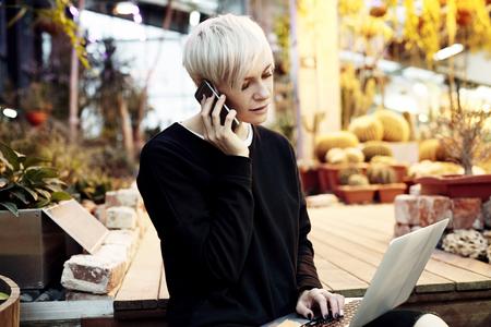 Jeune jolie femme hipster avec les cheveux courts blonds assis sur les escaliers, parler par téléphone mobile travaillant sur ordinateur portable. Été dans le parc ou un jardin botanique Banque d'images
