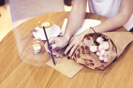 Close-up hipster businesswoman writing on envelope, sitting in cafe. Creative young girl drinking coffee, flowers on wooden table. Focus on fingers.
