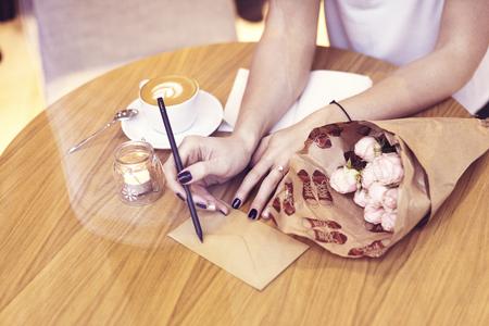 Close-up pantaloni a vita bassa imprenditrice scrivendo sulla busta, si siede in caffè. Creativo giovane ragazza bere caffè, fiori sul tavolo di legno. Concentrarsi sulle dita. Archivio Fotografico