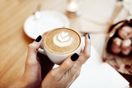 Cup of coffee cappuccino in woman hands, view from above, rose flowers in cafe