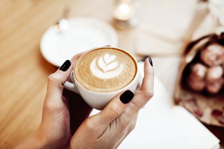Tazza di caffè cappuccino nelle mani di donna, vista dall'alto, di rosa fiori in cafe