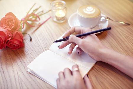 Le mani della donna del primo piano iscritto nel notebook, utilizzando matita, pagine bianche per il layout. Cappuccino caffè latte con il cuore in cima. Fiori sul tavolo di legno in caffetteria moderna. San Valentino celebrazione concetto