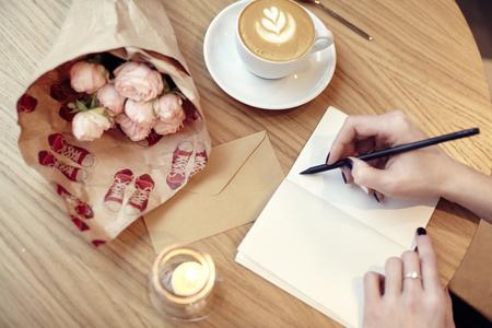 La mujer da el primer plano de la escritura en el cuaderno o una tarjeta postal, diseño en blanco para el diseño. Flores y café en el café en la mesa de madera, día de San Valentín