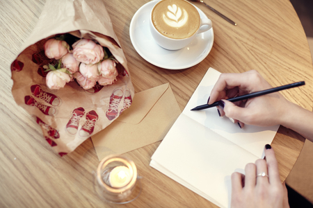 Woman hands close-up writing at notebook or postcard, blank layout for design. Flowers and coffee in cafe on wooden table, St. Valentines day Stock Photo