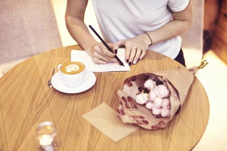 Close-up pantaloni a vita bassa imprenditrice che indossa bianco scrittura t-shirt in un caffè sul progetto di avvio. Creativa ragazza con notebook al tavolo di legno. Bere pausa caffè.