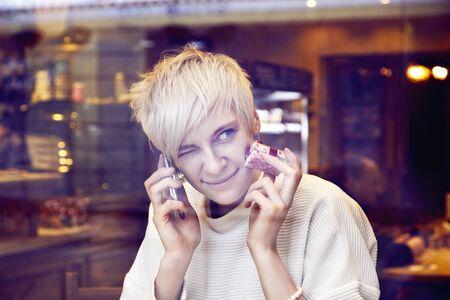 Blonde beautiful caucasian woman wearing white sweater sitting in cafe near window. Fanny face, squints one eye, wink. lady talking by mobile phone.
