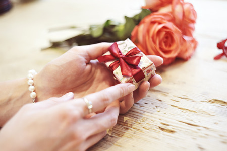 Small present box with bow in woman hands. Bracelet of pearls on hand. focus on bow. Red roses flowers behind on wooden table. St. Valentines day concept Stock Photo