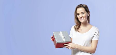 Smiling caucasian blonde woman with red present box. Celebration of St. Valentines day concept Stock Photo