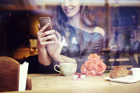Young caucasian woman with long hair sitting near window in cafe or restaurant, writing text message by phone, smiling and looking at screen. Celebrating St. Valentines day