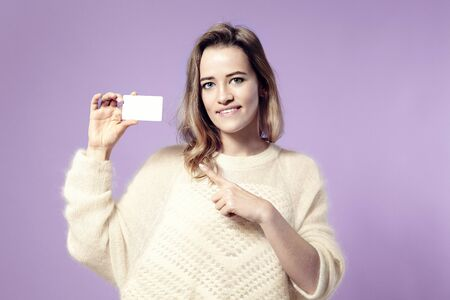 Portrait of european young smiling business woman holding credit card. isolated on violet background