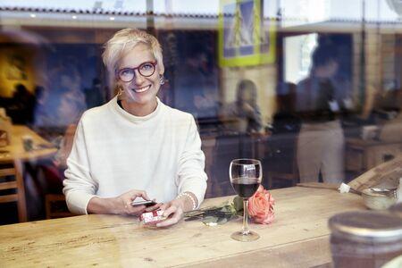 Bella donna bionda con gli occhiali cercando di fotocamera, utilizzando il telefono cellulare in caffè. Ha ottenuto un messaggio d'amore. Casella presente e fiori rosa su tavola di legno. prima colazione Romantique per una data o il giorno di San Valentino.