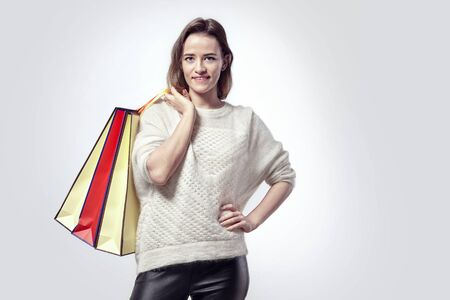 Blonde beautiful woman with shopping paper bags on shoulder. Calm emotions, caucasian face, sweater. Stock Photo