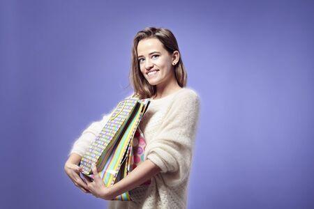 Bionda bella donna caucasica felice con presenti sacchetti di carta in mano. Indossando maglione caldo, emozioni felici. San Valentino concetto di giorno Archivio Fotografico