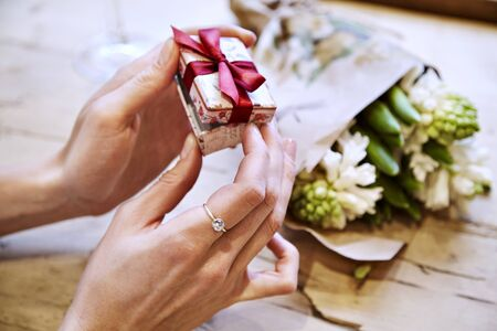 Close-up of woman hands opening a present box, celebrating Valentines Day, birthday. Bouquet of flowers on wooden table