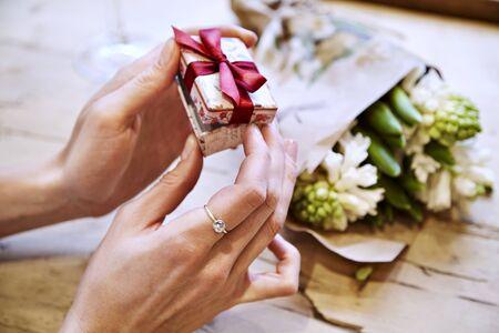 Primo piano delle mani della donna l'apertura di una casella presente, celebrando San Valentino, compleanno. Mazzo di fiori sul tavolo in legno