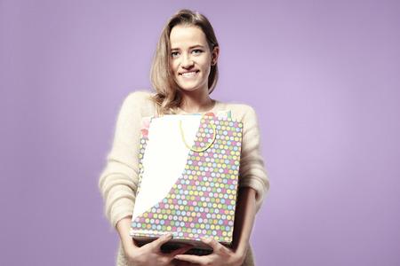 Bionda bella donna caucasica felice con presenti sacchetti di carta in mano. Indossando maglione caldo, emozioni felici. Isolato su sfondo viola