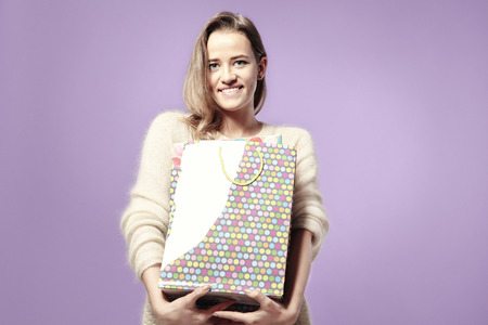 Blonde beautiful caucasian woman happy with present paper bags in hands. Wearing warm sweater, happy emotions. Isolated on violet background
