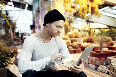 Handsome hippie portrait homme travaillant sur le projet de start-up sur ordinateur portable portable. Guy au chapeau noir regardant en avant dans un parc journée ensoleillée. concept de style de vie d'affaires