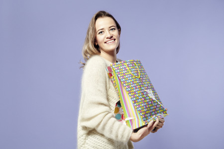 Blonde beautiful caucasian woman happy with present paper bags in hands. Wearing warm sweater, happy emotions. St. Valentines day concept