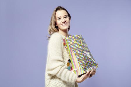 Blonde belle femme caucasien heureux avec présents sacs en papier dans les mains. Le port de chandail chaud, émotions heureuses. St. Valentines concept de jour Banque d'images