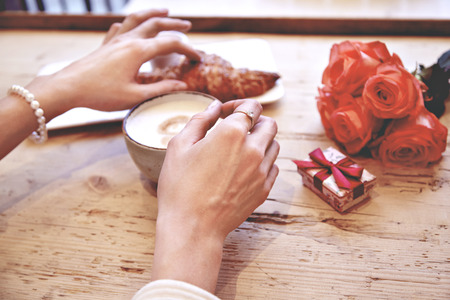Close-up of woman hands holding fresh croissant in cafe, celebrating Valentines Day, birthday. Bouquet of flowers on wooden table
