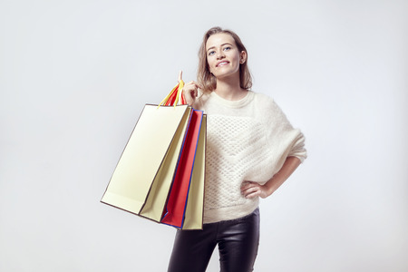 Blonde beautiful caucasian woman with shopping paper bags on shoulder. Wearing warm sweater, smiling.