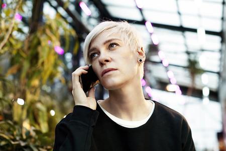 Portrait de hippie femme aux cheveux courts blonds parler par téléphone mobile. intérieur du jardin botanique intérieur ou parc d'été