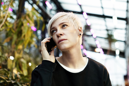 Portrait of  hipster woman with blonde short hair talking by mobile phone. Indoor botanical garden interior or summer park